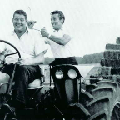 Tiger Tom and Tiny Lund on Tractor Hauling Hay.