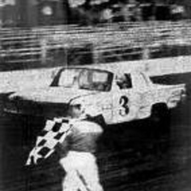being flagged the winner in number 3 IMCA Stock Carbigger