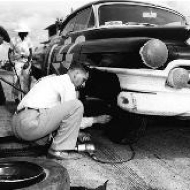 Raymond Parks changing tire on Red Byron's Cadillac - Darlington 1950